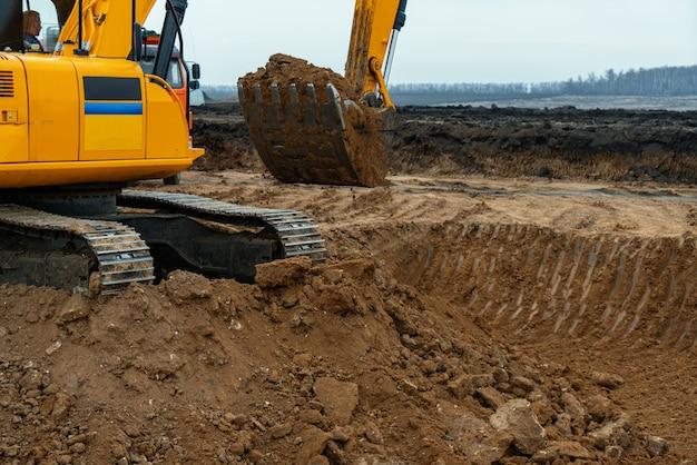 Uma grande escavadeira de construção de cor amarela no canteiro de obras em uma pedreira para extração de pedreiras. imagem industrial