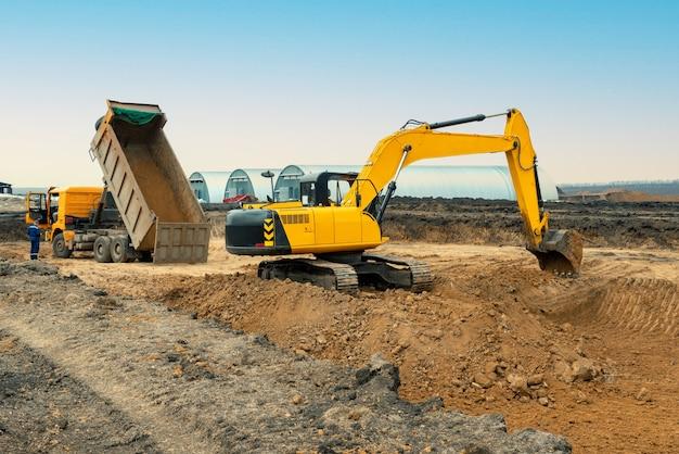 Uma grande escavadeira de cor amarela no canteiro de obras em uma pedreira para a extração
