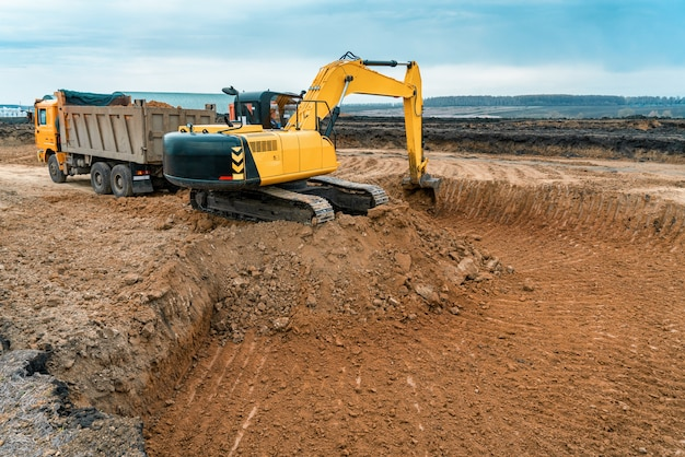 Uma grande escavadeira de cor amarela no canteiro de obras em uma pedreira para extração. imagem industrial.