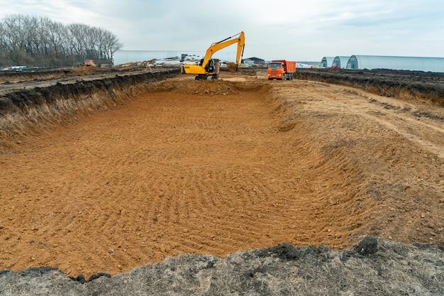 Uma grande escavadeira de cor amarela no canteiro de obras em uma pedreira para extração