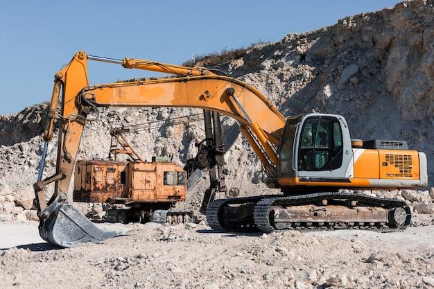 Uma grande escavadeira de esteira amarela está minerando rocha em uma pedreira.