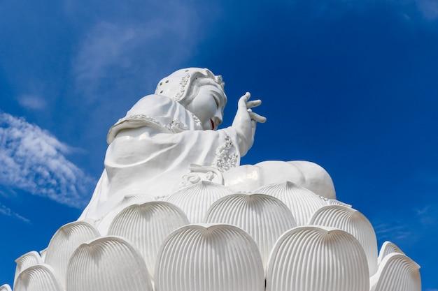 Uma grande estátua branca de guan yin atrás do céu e da luz solar no dia.