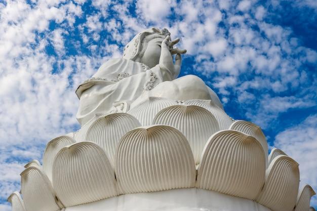 Uma grande estátua branca de guan yin no montanhês atrás do céu e da luz solar no dia.