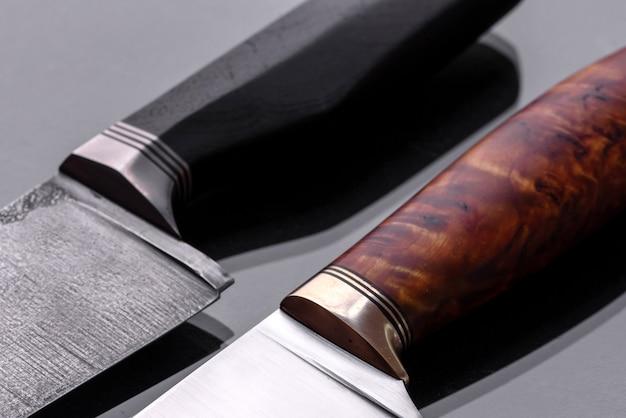 Uma grande faca de caça feita à mão sobre um fundo escuro e monótono