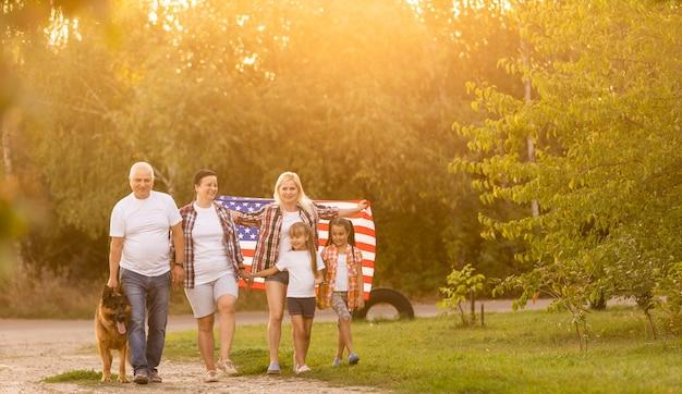 Uma grande família caminha andando com bandeiras americanas. vista frontal, patriotas americanos no prado do parque.