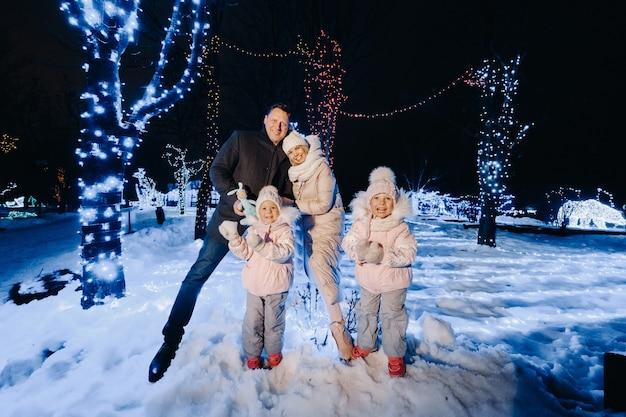 Uma grande família com filhos em uma cidade de natal à noite com luzes noturnas