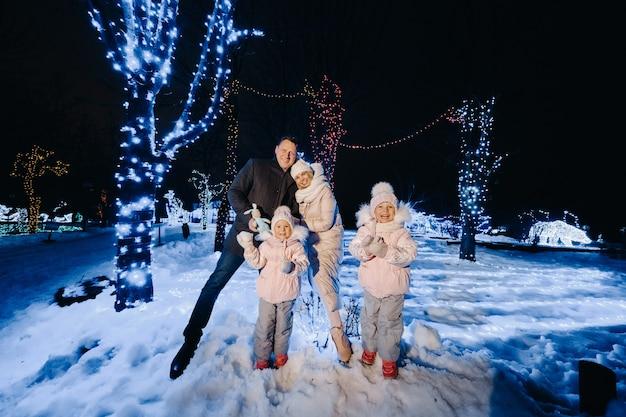 Uma grande família com filhos em uma cidade natalina à noite com luzes noturnas