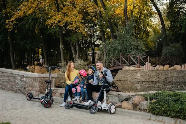 Uma grande família feliz anda de segways e scooters elétricos no parque em um dia quente de outono durante o pôr do sol.