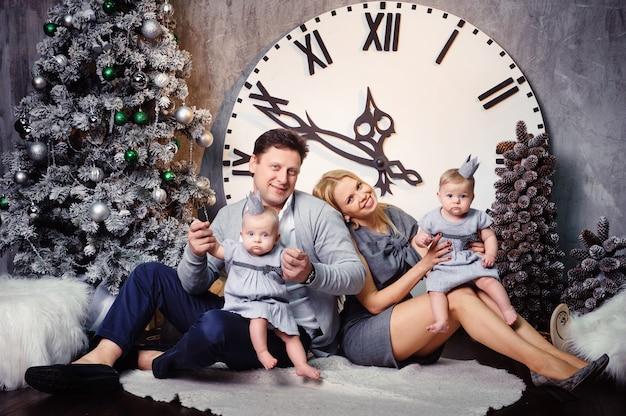 Uma grande família feliz com filhos gêmeos no interior da casa de ano novo contra o fundo de um grande relógio