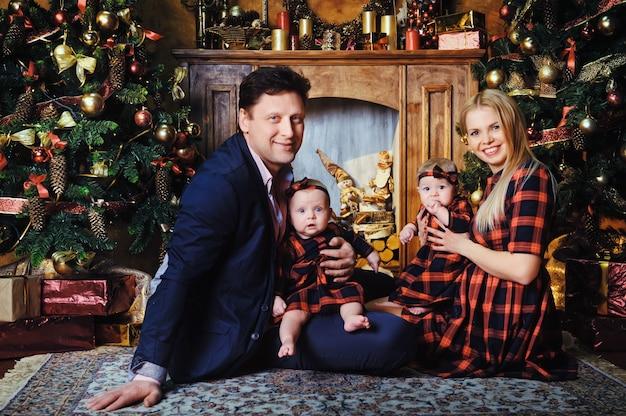 Uma grande família feliz com seus filhos no interior da casa de ano novo perto da lareira ao lado da árvore de natal