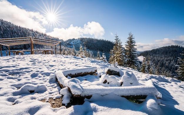 Uma grande fogueira coberta de neve para caminhadas nas montanhas dos cárpatos. sol forte e frio