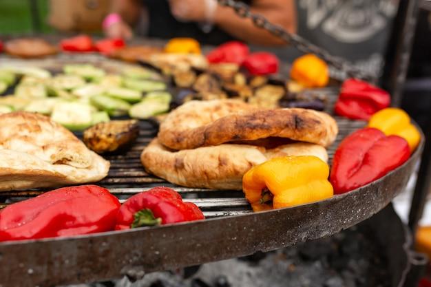 Uma grande grelha redonda sobre as brasas nas quais são cozidos legumes coloridos grelhados e salsichas de carne fresca.