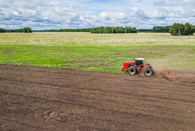 Uma grande máquina agrícola cultiva a terra. a vista do topo. arar a terra para o plantio. fotos da visão aérea com um quadricóptero