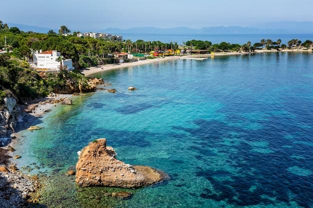Uma grande pedra em forma de coração no mar azul turquesa e na costa verde em um dia ensolarado. excelente vista para a bela baía. relaxe e tranquilidade. cartão postal. espaço para texto.