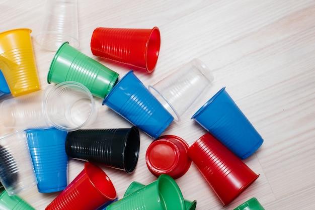 Uma grande pilha de copos de plástico multicoloridos espalhados pelo chão com espaço livre. poluição do meio ambiente por dejetos humanos.