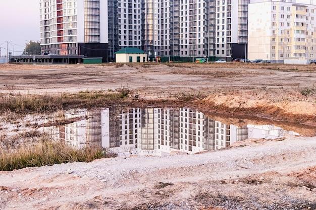 Uma grande poça após a chuva no canteiro de obras de uma grande instalação residencial. reflexo na água do canteiro de obras e guindastes no contexto do céu do sol.