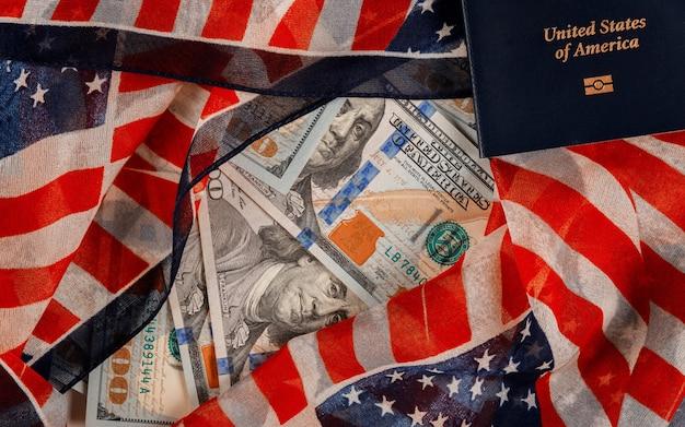 Uma grande quantidade de dinheiro de us $ 100 em passaportes americanos no símbolo nacional da bandeira dos eua
