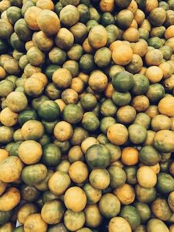 Uma grande quantidade de limas verdes e amarelas. conceito vegetariano, vegano, saudável e de verão