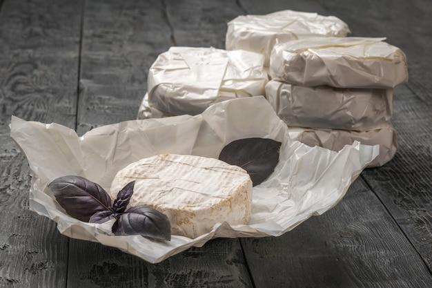 Uma grande quantidade de queijo camembert e folhas de manjericão roxo em uma mesa de madeira.