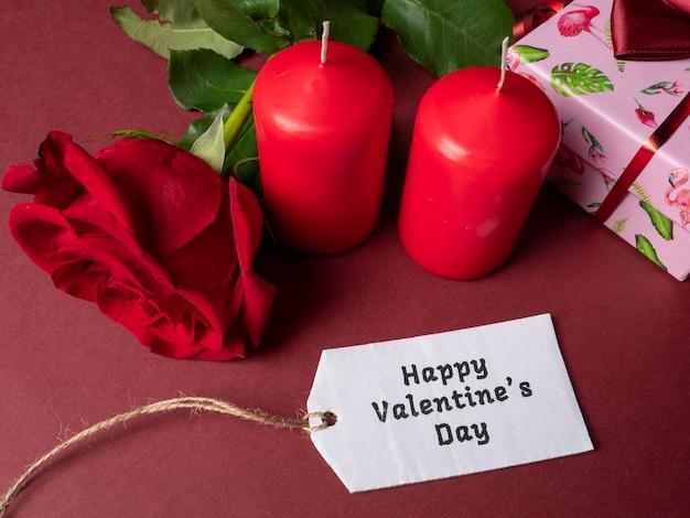 Uma grande rosa vermelha que está ao lado de duas grandes velas vermelhas e uma rosa