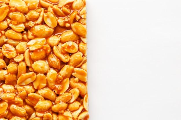 Uma grande telha de amendoim torrado bar em um melaço doce. kozinaki doces úteis e saborosos do oriente