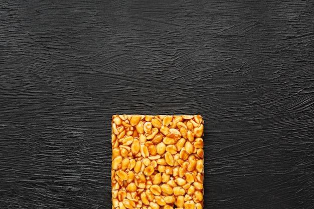 Uma grande telha dourada de amendoim, um bar em um melaço doce. kozinaki doces úteis e saborosos do oriente