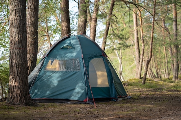 Uma grande tenda para turistas é montada no acampamento em uma bela floresta à beira do lago