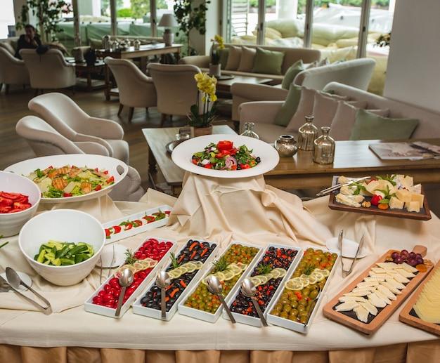 Uma grande variedade de aperitivos, incluindo variedades de azeitona, queijo e salada.