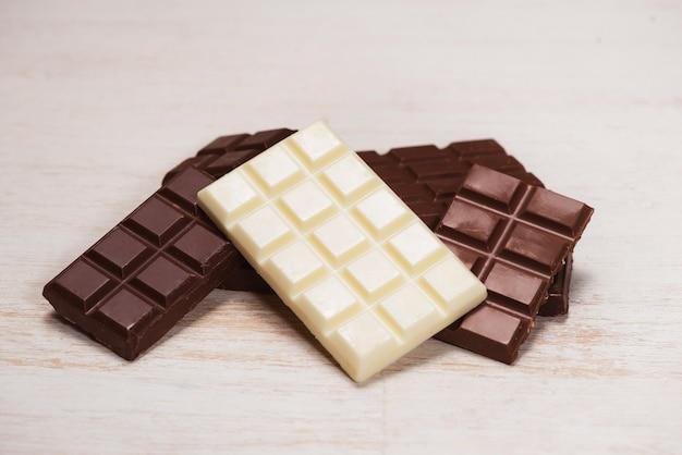 Uma grande variedade de barra de chocolates em caixa com fundo branco de madeira