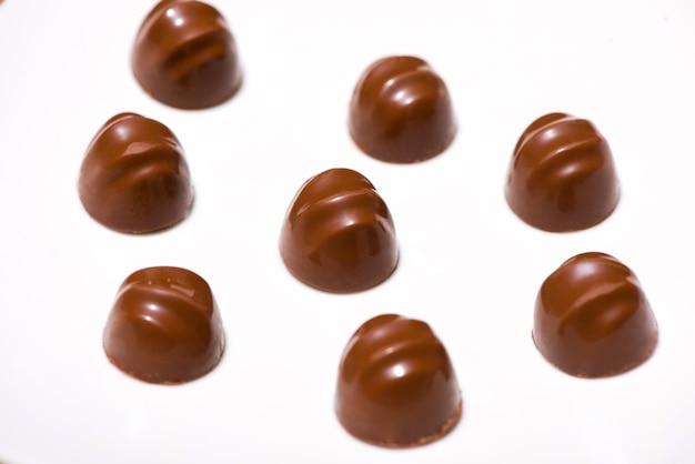 Uma grande variedade de chocolates em fundo branco de madeira