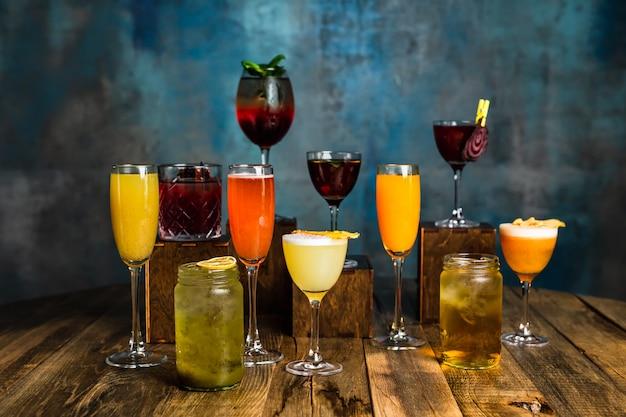 Uma grande variedade de coquetéis alcoólicos em copos diferentes em uma superfície de madeira