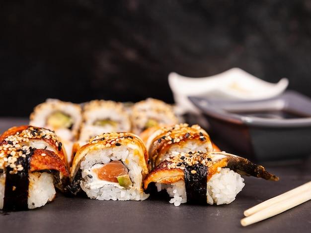 Uma grande variedade de rolos de sushi em fundo de pedra preta em foto de estúdio