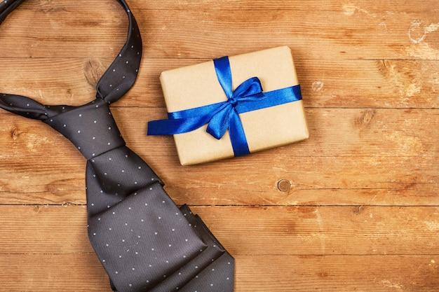 Uma gravata cinza e um presente em uma mesa de madeira