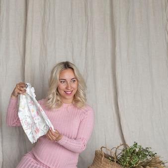 Uma grávida segura roupas para um recém-nascido. copie o espaço