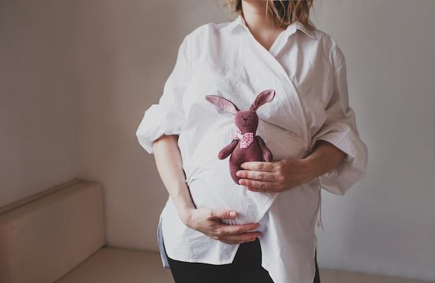 Uma grávida segura um brinquedo macio perto da barriga. mãe feliz. esperando a gravidez.
