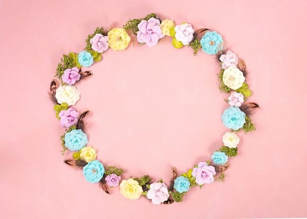 Uma grinalda de flores de papel multicoloridas no fundo coral vivo. dia dos namorados. conceito de amor. clima de primavera. espaço para texto. faixa larga - imagem.