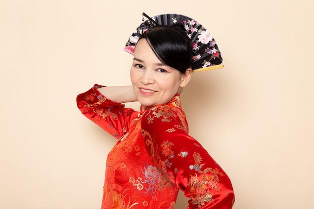 Uma gueixa japonesa requintada vista frontal no tradicional vestido japonês vermelho com varas de cabelo posando segurando ventilador dobrável elegante sorrindo sobre a cerimônia de creme de fundo japão