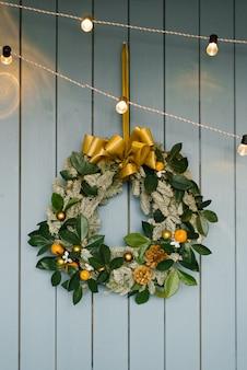 Uma guirlanda de árvore de natal paira sobre uma parede de madeira azul empoeirada