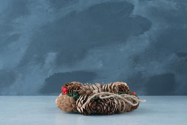 Uma guirlanda de natal de pinha em fundo de mármore. foto de alta qualidade