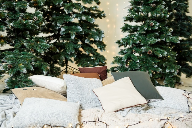 Uma guirlanda de natal dos galhos de uma árvore de natal está pendurada na parede. decorações da casa para o ano novo. decorações no quarto para os feriados de ano novo