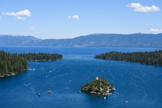 Uma ilha isolada no oceano, cercada por ilhas de abetos e altas montanhas rochosas
