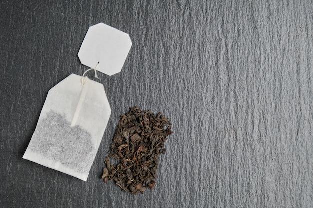 Uma imagem abstrata do conteúdo de um saco de chá preto no contexto de uma placa de ardósia.