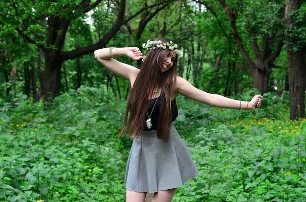 Uma imagem da floresta de uma morena nova bonita da aparência européia com os olhos marrons escuros e os bordos grandes. na cabeça da menina está usando uma coroa de flores, na testa decorações brilhantes