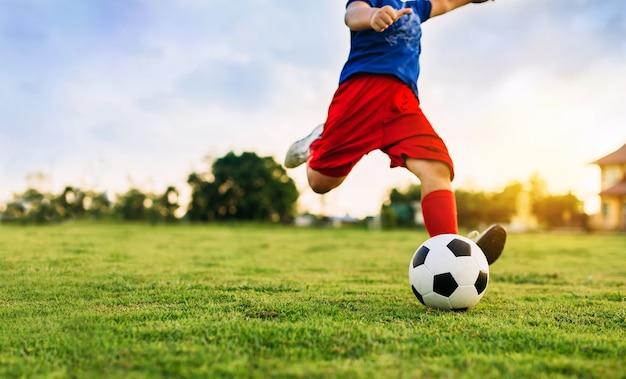 Uma imagem de esporte de ação do garoto jogando futebol para o exercício em comunidade sob o