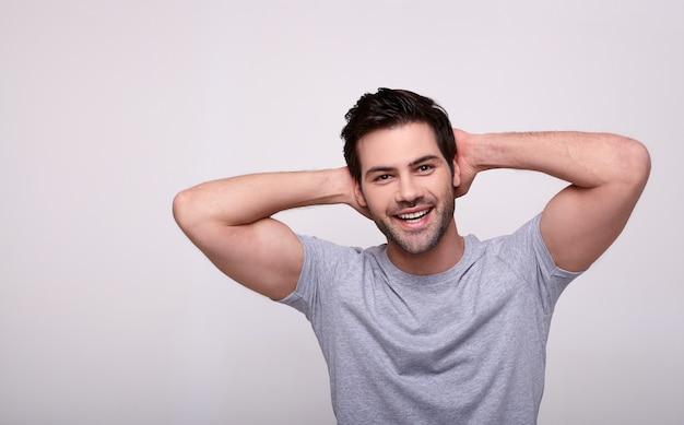 Uma imagem de um jovem feliz e bombeado em uma camiseta cinza.