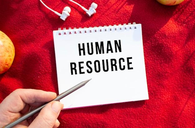 Uma imagem de uma mão escrevendo com um lápis em um caderno branco sobre uma manta vermelha na natureza. texto no caderno recursos humanos. conceito de design.