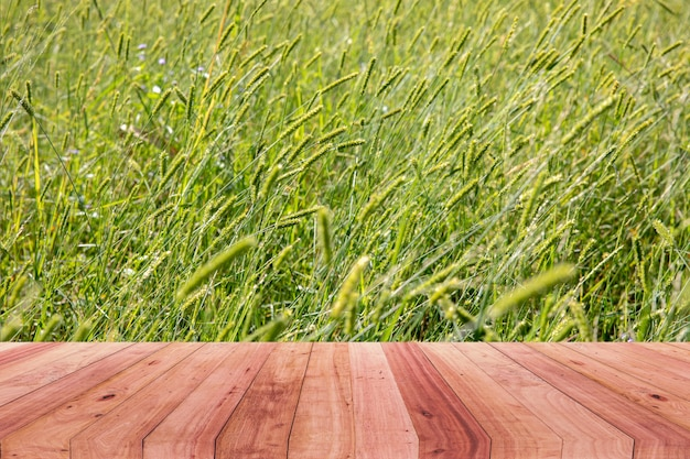 Uma imagem de uma mesa de madeira na frente de um fundo abstrato de uma flor da grama.