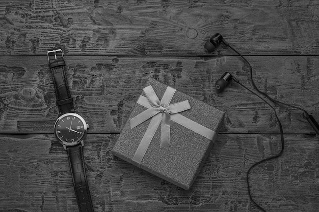 Uma imagem em preto e branco de um relógio, fones de ouvido e gravata em uma superfície de madeira. acessórios de moda masculina.