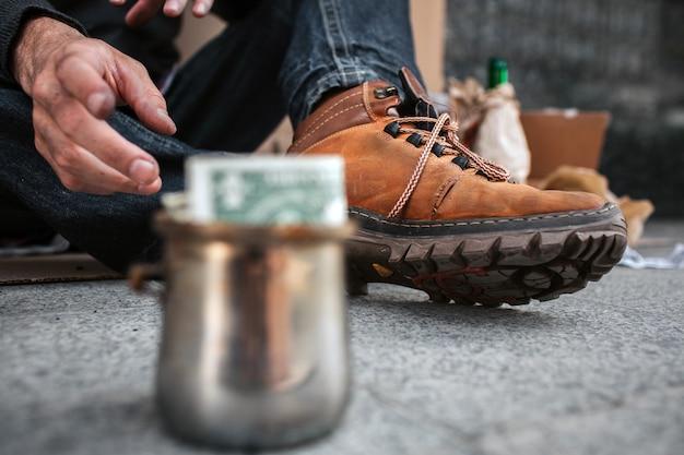 Uma imagem focada em botas e na mão suja de um sem-teto. ele está alcançando um copo que está na sua frente. há um dólar neste copo de metal.
