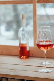 Uma imagem vertical de garrafa de vinho rosé e dois copos